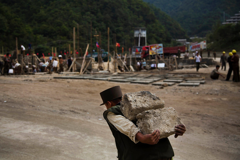 ". A North Korean construction worker carries bricks at a building project to construct a ski resort at North Korea\'s Masik Pass on Friday Sept. 20, 2013. North Korean authorities have been encouraging a broader interest in sports and recreation in the country, calling it ""the hot wind of sports blowing through Korea.\""   (AP Photo/David Guttenfelder)"