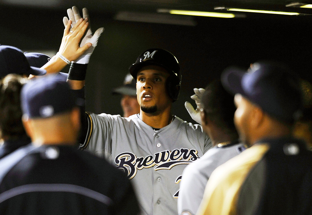 . Milwaukee Brewers Carlos Gomez is congratulated by teammates after his solo home run in the ninth inning of a baseball game against the Colorado Rockies, Friday, July 26, 2013, in Denver. The Rockies won 8-3. (AP Photo/Chris Schneider)