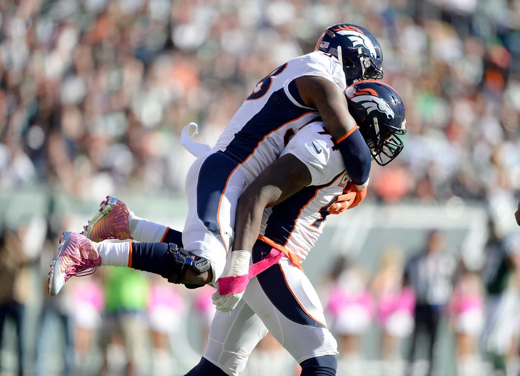 . Denver Broncos outside linebacker Von Miller (58) celebrates Denver Broncos defensive end DeMarcus Ware (94) sack on New York Jets quarterback Geno Smith (7) during the third quarter  October 12, 2014 at Metlife Stadium. (Photo by John Leyba/The Denver Post)