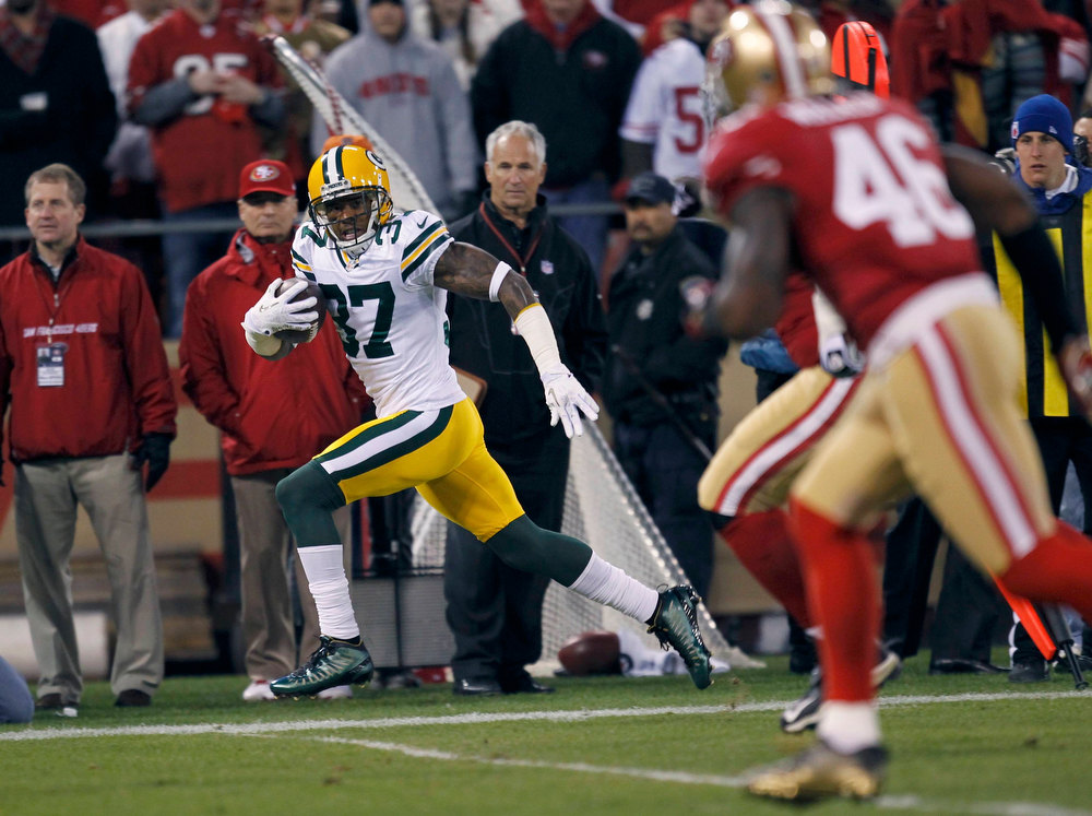 Description of . Green Bay Packers Sam Shields (L) runs past San Francisco 49ers Delanie Walker (R) as he takes an interception in for a touchdown in the first quarter during their NFL NFC Divisional playoff football game in San Francisco, California January 12, 2013. REUTERS/Robert Galbraith