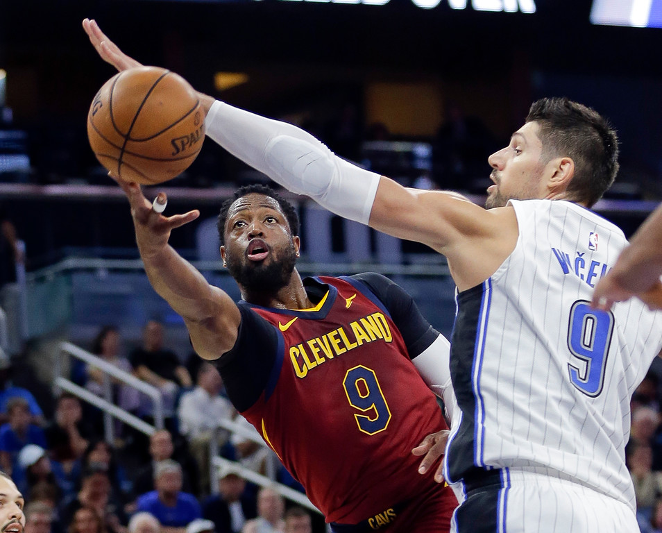 . Cleveland Cavaliers\' Dwyane Wade, let, makes a basket as he gets past Orlando Magic center Nikola Vucevic during the first half of an NBA preseason basketball game, Friday, Oct. 13, 2017, in Orlando, Fla. (AP Photo/John Raoux)