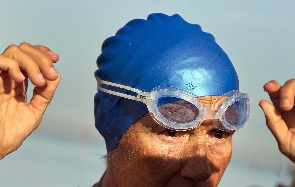 . U.S. swimmer Diana Nyad, 64, adjusts her goggles before jumping into the water to start her swim to Florida from Havana, Cuba, Saturday, Aug. 31, 2013. Endurance athlete Nyad launched another bid Saturday to set an open-water record by swimming from Havana to the Florida Keys without a protective shark cage.   (AP Photo/Ramon Espinosa)