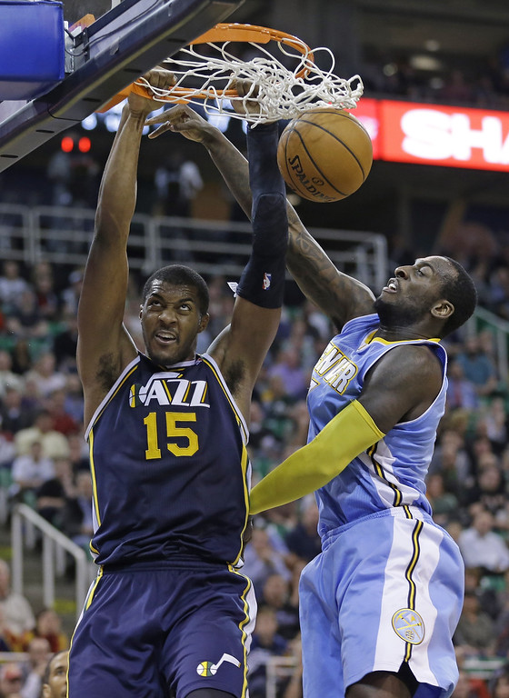 . Utah Jazz\'s Derrick Favors (15) dunks the ball on Denver Nuggets\' J.J. Hickson (7) in the fourth quarter during an NBA basketball game Monday, Nov. 11, 2013, in Salt Lake City. The Denver Nuggets won 100-81. (AP Photo/Rick Bowmer)