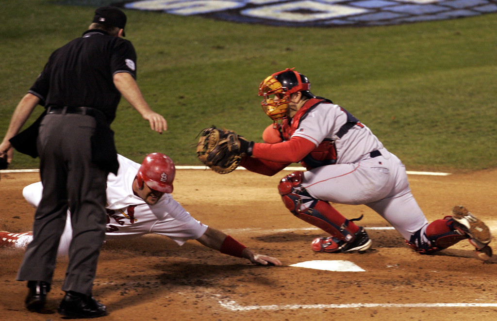 . Home plate umpire Brian Gorman watches as Boston Red Sox catcher Jason Varitek reaches to tag out St. Louis Cardinals Larry Walker to end the first inning during Game 3 of the World Series at Busch Stadium in St. Louis, Tuesday, Oct. 26, 2004.  (AP Photo/Mark Humphrey)