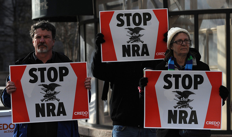 . People protest the National Rifle Association of America (NRA) news conference in front of the Willard Hotel, near the White House December 21, 2012 in Washington, DC. The nation\'s largest gun lobby called Friday for Congress to require armed security guards in every school, saying it would help prevent such acts of mass violence from happening again. (Olivier Douliery/Abaca Press/MCT)