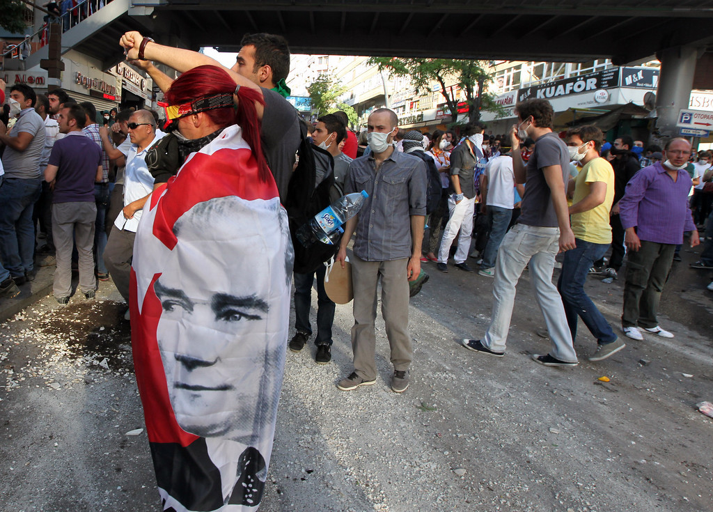 . Turkish youths, one with a national flag adorned with a poster of Kemal Ataturk, Turkey\'s founder, in Ankara, Turkey, Saturday, June 1, 2013. Turkish police retreated from a main Istanbul square Saturday, removing barricades and allowing in thousands of protesters in a move to calm tensions after furious anti-government protests turned the city center into a battlefield. A second day of national protests over a  violent police raid of an anti-development sit-in in Taksim square has revealed the depths of anger against Prime Minister Recep Tayyip Erdogan, who many Turks view as increasingly authoritarian and dismissive of opposing views.(AP Photo/Burhan Ozbilici)