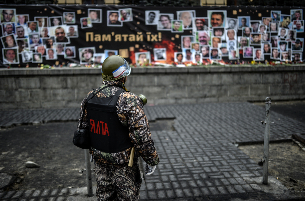 ". A member of a so-called ""Maidan\'s self defense unit\"" looks at pictures of protesters who were killed during recent clashes, displayed in central Kiev on March 1, 2014. Ukraine\'s defense chief accused Russia on March 1, 2014 of sending 6,000 troops and 30 armoured personnel carriers into Crimea as the restive peninsula tries to gain broader independence from new pro-EU leaders in Kiev. (BULENT KILIC/AFP/Getty Images)"