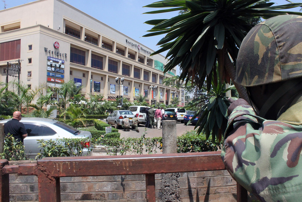 . A soldier aims his weapon outside the Westgate Mall, an upscale shopping mall  in Nairobi, Kenya Saturday Sept. 21 2013, where shooting erupted when armed men staged an attack.   (AP Photo/Jason Straziuso)