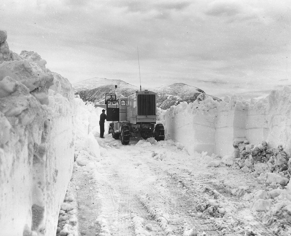""". The operator of a \""""Sno-Go� machine checks the blades of his rotary plow in a cut he is making through eight-foot snowdrifts atop Trail Ridge Road, Rocky Mountain National Park in Colorado, 1955. (Donald C Cieber/The Denver Post)"""