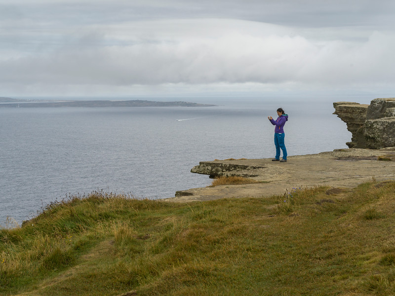 Woman taking picture on mobile phone, Cliffs of Moher, Ennistimon, County Clare, Republic of Ireland