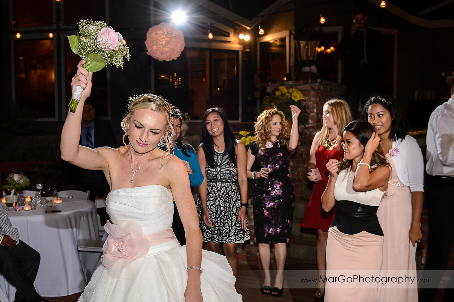 bride tossing the bouquet during backyard wedding reception