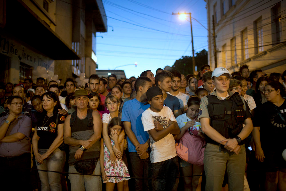Description of . People gather outside the Kiss nightclub honoring the victims of early Sunday's fatal fire inside the club in Santa Maria, Brazil, Monday, Jan. 28, 2013. All the elements were in place for the tragedy at the Kiss nightclub early Sunday. The result was the world's worst fire of its kind in more than a decade, with 231 people dead and this southern Brazilian college town in shock and mourning.(AP Photo/Felipe Dana)