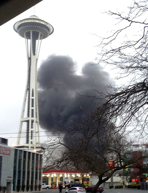 . In this photo provided by KIRO- TV,  smoke rises at the scene of a helicopter crash outside the KOMO-TV studios near the space needle in Seattle on Tuesday, March 18, 2014.   (AP Photo/KIRO-TV)