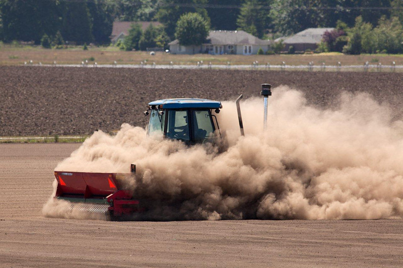 Wind borne soil particles arising from farming on a commercial sod farm.