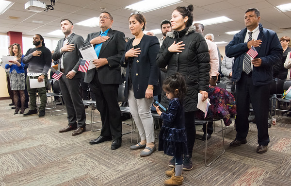 04/10/18 Wesley Bunnell | Staff New U.S. Citizens recite the Pledge of Allegiance including Dritero Cerati from Macedonia, 3rd from L, Tito Fernandez Benitez from Paraguay, Patricia Santos Guillen from Peru, 1st row far R, as she stands with her daughter Skyler, age 3, and Ancizar Uran Rico from Colombia, far right 2nd row. The New Britain Public Library held a naturalization ceremony on Tuesday afternoon for CT residents.