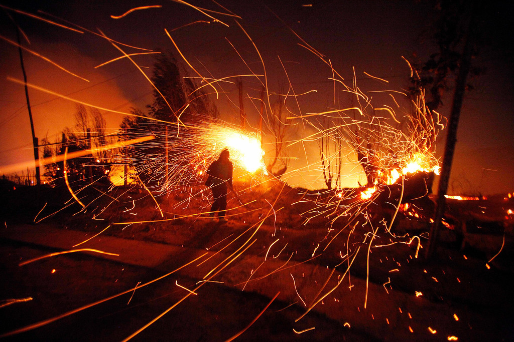 . A person tries to extinguish flames as sparks fly during a wild forest fire in Valparaiso, Chile, Sunday April 13, 2014. Authorities say the fires have destroyed hundreds of homes, forced the evacuation of thousands and claimed the lives of at least seven people.  ( AP Photo/ Luis Hidalgo)