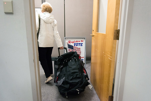 11/06/18 Wesley Bunnell | Staff Pat Coyle, Moderator at the Roosevelt Middle School voting site, pulls a wheeled bag containing the voting ballots from her site into New Britain City Hall late Tuesday night.