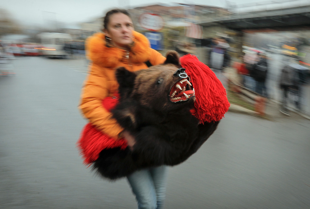 . A woman carries a dancer\'s costume made of a bear\'s fur before a parade of new year\'s traditions in Comanesti, northern Romania, Saturday, Dec. 30, 2017. The tradition, originating in pre-Christian times, when dancers wearing colored costumes or animal furs, went from house to house in villages singing and dancing to ward off evil, has moved to Romania\'s cities, where dancers travel to perform the ritual for money.(AP Photo/Vadim Ghirda)(AP Photo/Vadim Ghirda)