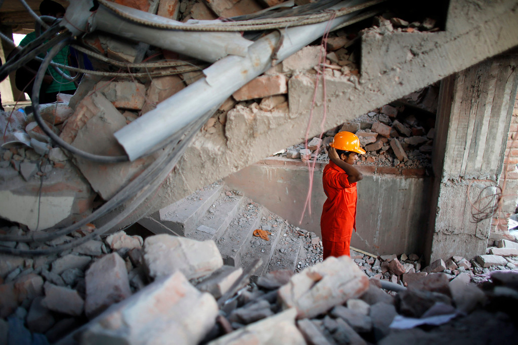 . A rescue worker stands among the rubble as he takes part in the rescue process after the Rana Plaza building collapsed, in Savar, 30 km (19 miles) outside Dhaka April 24, 2013. REUTERS/Andrew Biraj