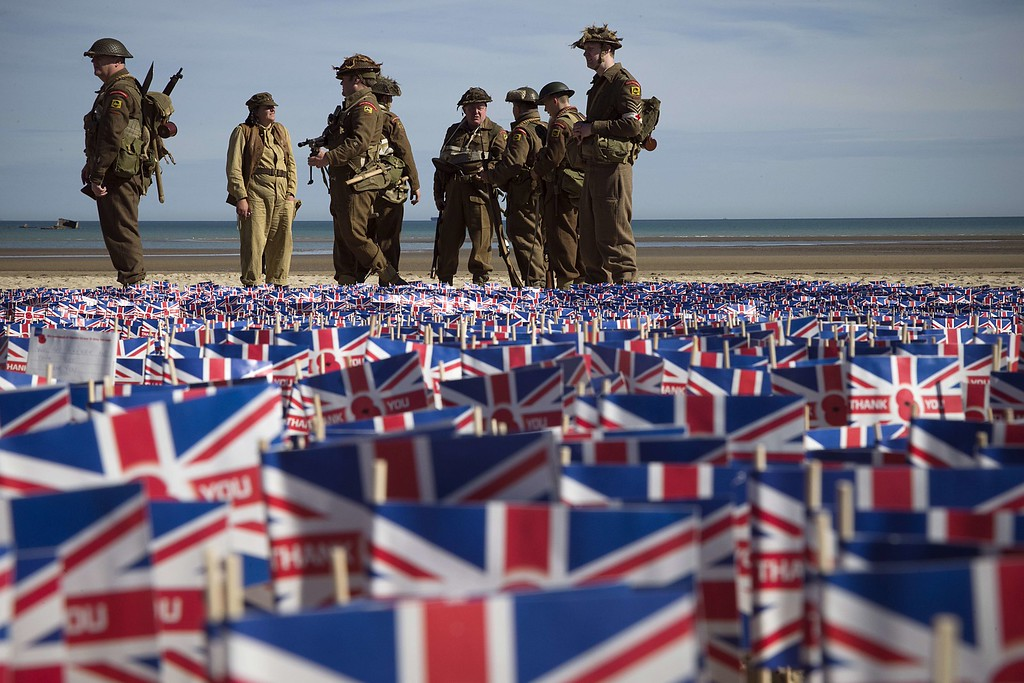 """. People wearing WWII British uniforms stand in front of British national flags on June 6, 2014 in Asnelles, Normandy, during a ceremony on the \""""Gold beach\"""" where British troops landed on June 6, 1944 during the Operation Overlord.    AFP PHOTO / JOEL SAGET/AFP/Getty Images"""