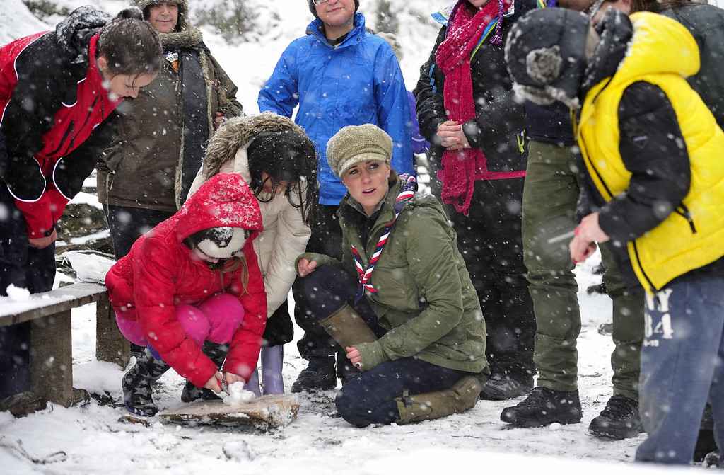 . Catherine, Duchess of Cambridge (C) offers assistance in firelighting during a visit to the Great Tower Scout camp at Newby Bridge in Cumbria on March 22, 2013.   The Duchess braved snowy conditions to pay a visit to the scout camp.  ANDY STENNING/AFP/Getty Images