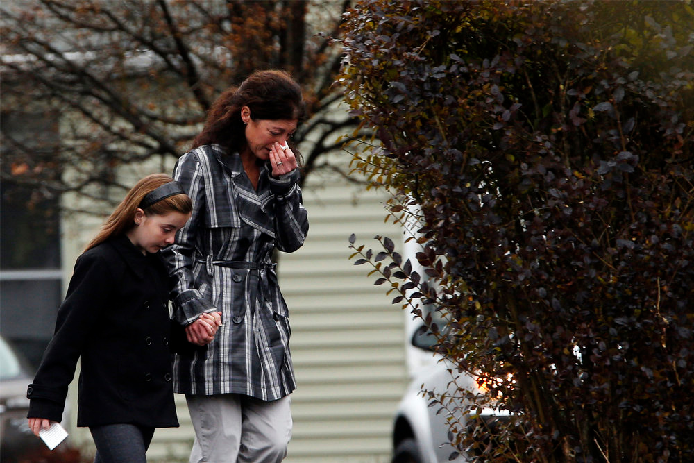 Description of . Mourners weep as they leave the Honan Funeral Home, where the family of six-year-old Jack Pinto is holding his funeral service, in Newtown, Connecticut December 17, 2012. Pinto was one of the 20 students killed in the December 14 shootings at Sandy Hook Elementary School in Newtown. REUTERS/Mike Segar