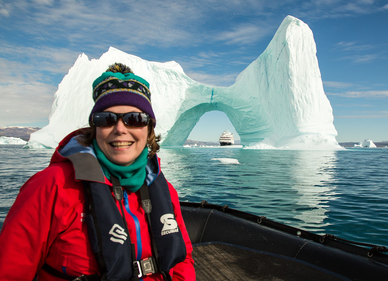 Women smiles as she sits in a raft in front of an iceberg.
