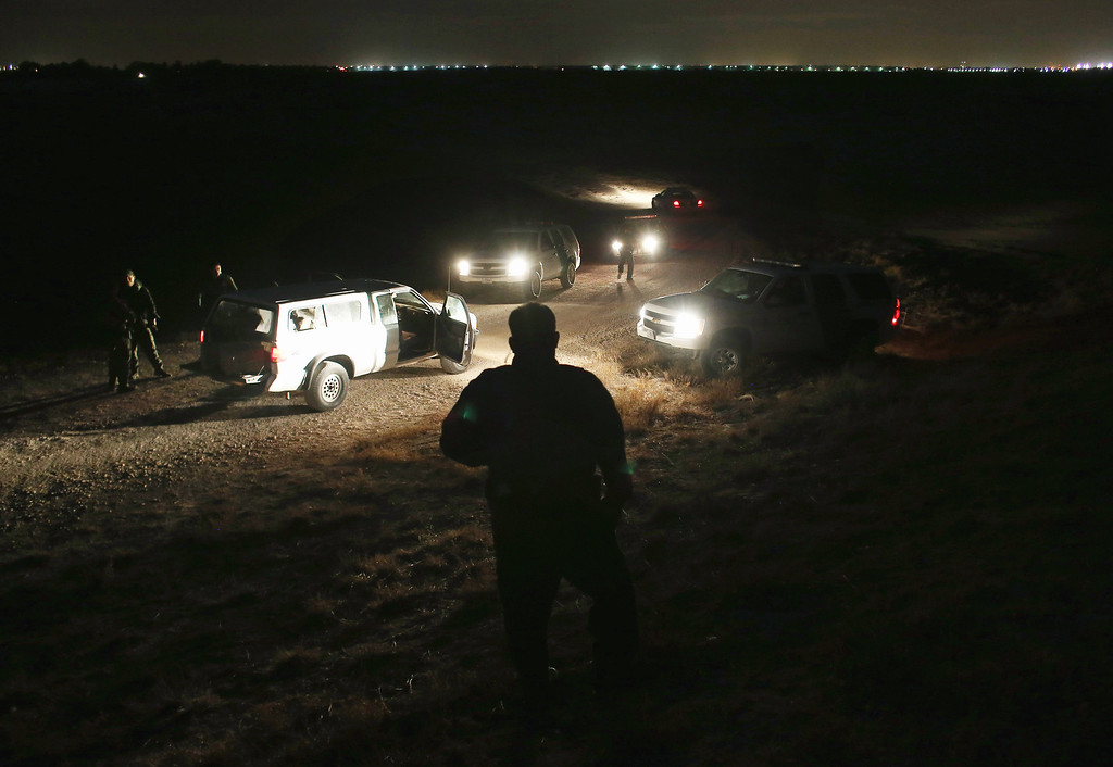 . MCALLEN, TX - APRIL 10:  U.S. Border Patrol agents inspect a pickup load (L), of marijuana seized from drug smugglers near the U.S.-Mexico border on April 10, 2013 in Hidalgo, Texas. The agents, guided by helicopter surveillance from the U.S. Office of Air and Marine, waited more than four hours in hiding before seizing more than 900 pounds of the drug. The smugglers ran and escaped by swimming back across the Rio Grande River into Mexico. Border Patrol agents say they have also seen an additional surge in immigrant traffic since immigration reform negotiations began this year in Washington D.C. Proposed refoms could provide a path to citizenship for many of the estimated 11 million undocumented workers living in the United States.  (Photo by John Moore/Getty Images)