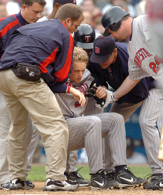 . Twins players, coaches and trainers lift Justin Morneau to his feet after he was hit in the head by a pitch thrown by Seattle\'s Ron Villone in the eighth inning on April 6, 2005 at Safeco Field. (File photo)