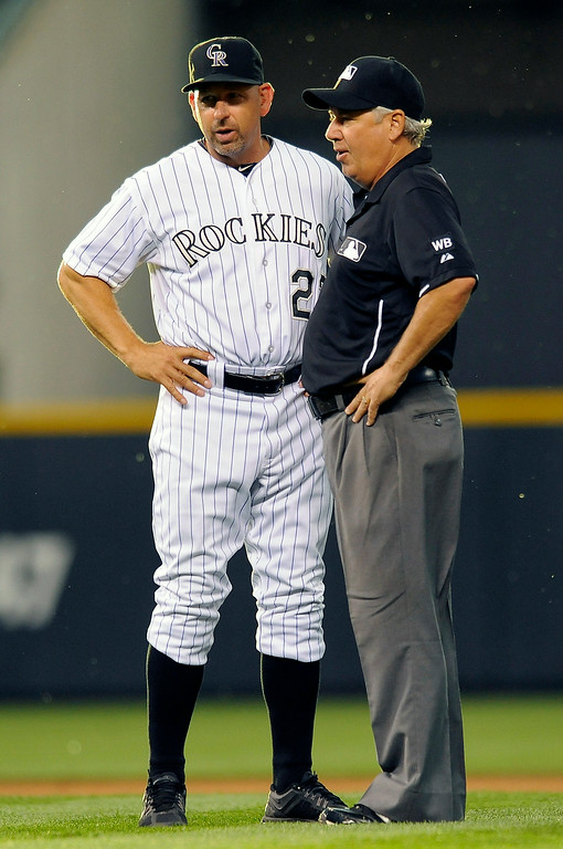 . Colorado Rockies manager Walt Weiss, left, talks with second base umpire Tom Hallion to argue that Pittsburgh Pirates\' Russell Martin was out at second base in the fifth inning of a baseball game on Friday, July 25, 2014, in Denver. The play was reviewed and Martin was ruled safe at second base which averted a triple play. (AP Photo/Chris Schneider)