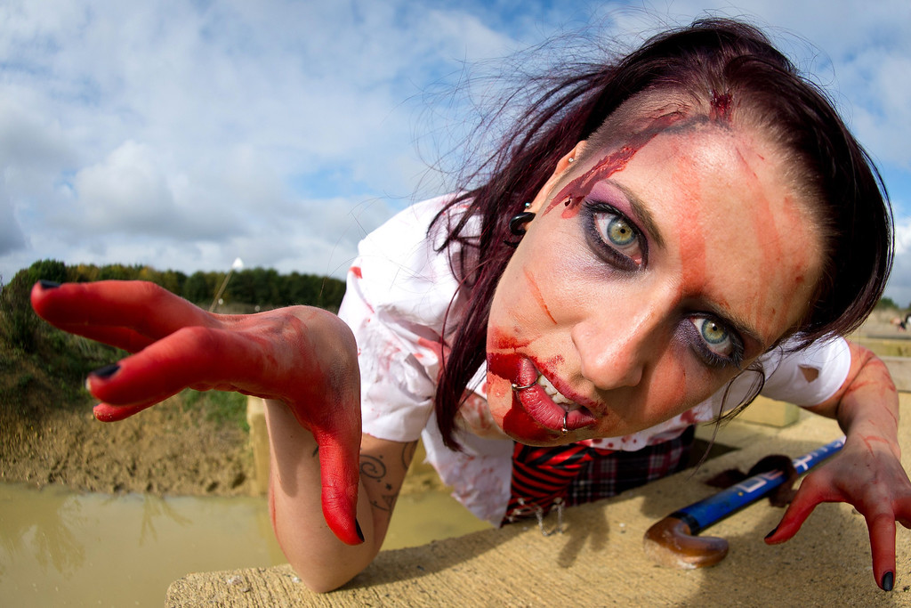 """. A zombie school girl poses for a picture as she prepares to take part in one of Britain\'s biggest horror events, the \""""Zombie Evacuation Race\"""" at Carver Barracks near Saffron Walden, England, on October 5, 2013. The race sees thousands of participants attempt to complete a gruelling 5 kilometre cross-country run, while evading \""""zombies\"""", intent on snatching the three life-line strips hanging from every runner\'s waist.  Those who manage to get through with any strips remaining are named as survivors while those without take home an \""""infected\"""" badge.  LEON NEAL/AFP/Getty Images"""