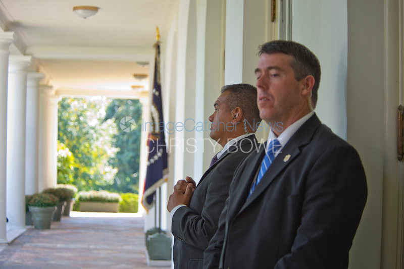 Presidential Protective Secret Service Agents stand guard on the Colonnade near the Oval Office.