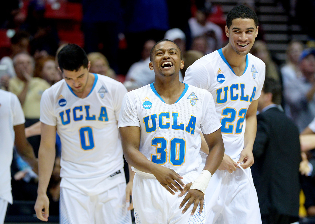 . Aubrey Williams #30 Nick Kazemi #0 and Noah Allen #22 of the UCLA Bruins celebrate their 77 to 60 win over the Stephen F. Austin Lumberjacks during the third round of the 2014 NCAA Men\'s Basketball Tournament at Viejas Arena on March 23, 2014 in San Diego, California.  (Photo by Donald Miralle/Getty Images)