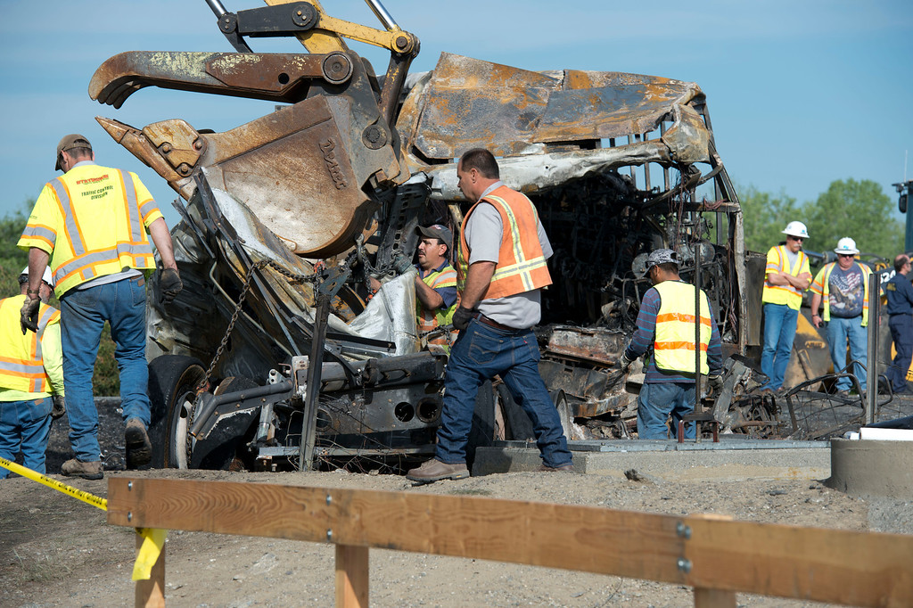 . Workers begin clearing the charred remains of a charter bus that collided with a FedEx truck on Thursday at Interstate 5 in Orland, Calif. Friday, April 10, 2014. At least ten people were killed and dozens injured in the fiery crash,Thursday, between a FedEx truck and a bus carrying high school students on a visit to a Northern California College.  (AP Photo/The Sacramento Bee, Hector Amezcua)  MAGS OUT; LOCAL TV OUT (KCRA3, KXTV10, KOVR13, KUVS19, KMAZ31, KTXL40); MANDATORY CREDIT