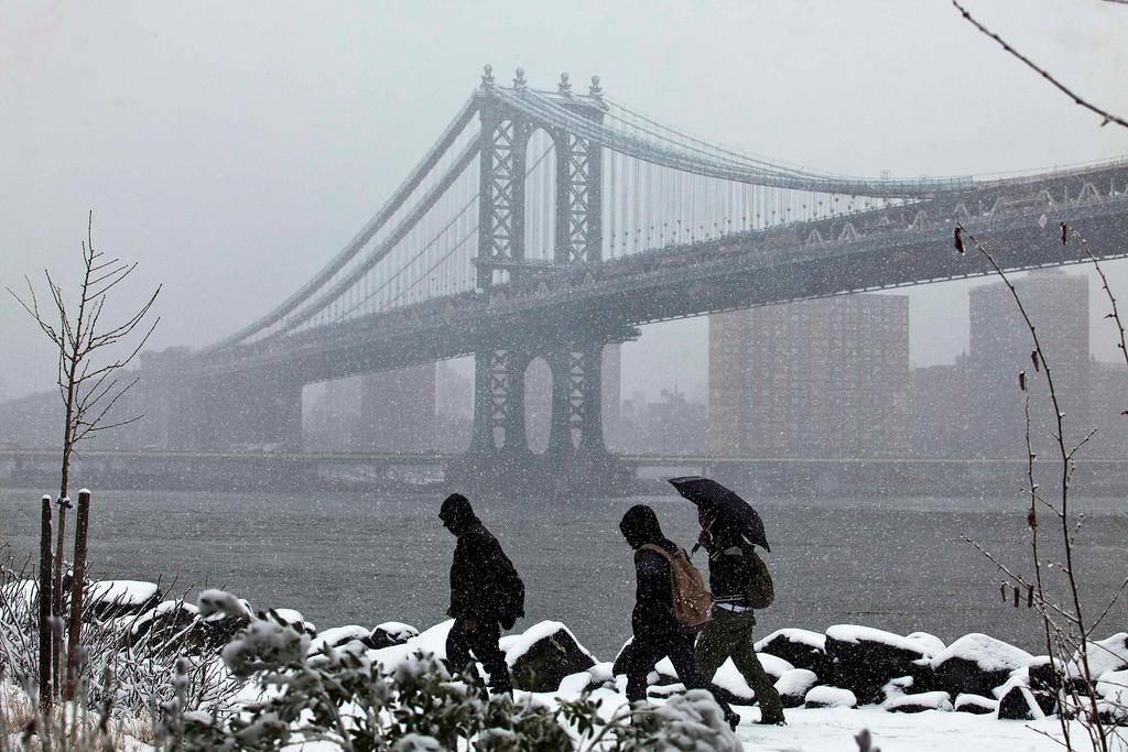 . People walk through Brooklyn Bridge Park as the skyline of New York and Manhattan bridge are seen during a snowstorm in New York March 8, 2013. REUTERS/Eduardo Munoz