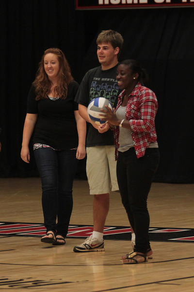Students line up for a chance to win a free pizza by serving the ball over the net.