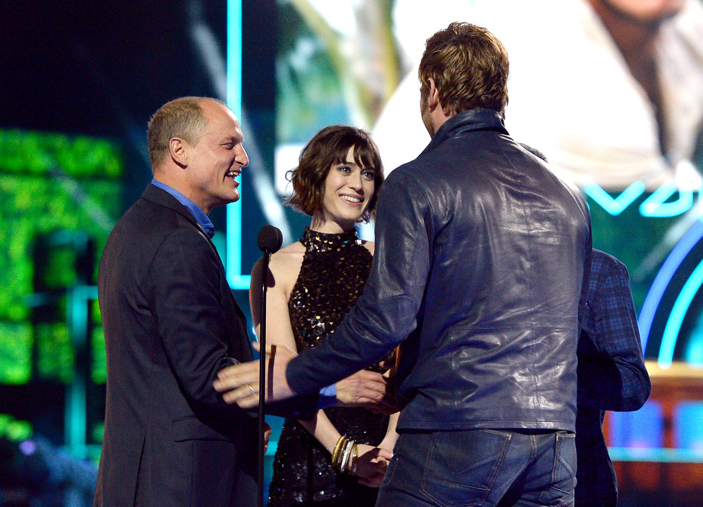 . Woody Harrelson, from left, Lizzy Caplan and Jesse Eisenberg present the award for best action performance to Chris Pratt, in foreground, at the MTV Movie Awards at Warner Bros. Studio on Saturday, April 9, 2016, in Burbank, Calif. (Kevork Djansezian/Pool Photo via AP)