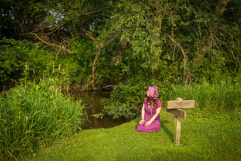 Becky, wearing her bonnet, sits on her knees smiling and looking around next to Plum Creek. A short wooden sign points the way to the spring and the dugout.