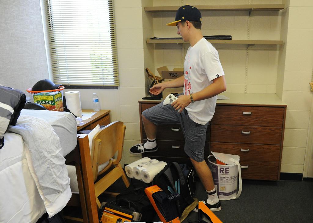 . (John Valenzuela/Staff Photographer) Freshman student John White of Burbank, unpacks in his new dorm room, Wednesday morning during move-in day at the University of Redlands, August 28, 2013.