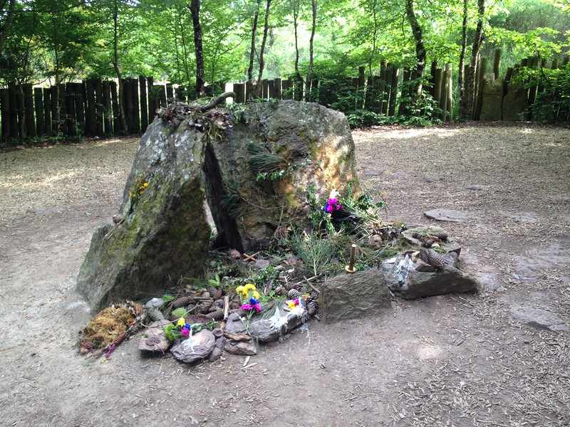 Broken stone covered with flowers and candles.