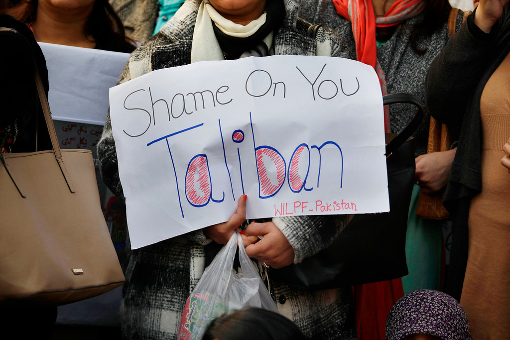 . A member of a civil society group holds an anti-Taliban placard to condemn Tuesday\'s Taliban attack on a military-run school in Peshawar, as members of multiple groups join a demonstration Wednesday, Dec. 17, 2014 in Islamabad, Pakistan. Pakistan mourned as the nation prepares for mass funerals Wednesday for over 140 people, most of them children, killed in the Taliban massacre in a military-run school in the countryís northwest in the deadliest and most horrific attacks in years, officials said. (AP Photo/Anjum Naveed)