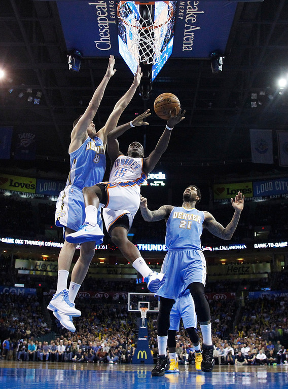 . Oklahoma City Thunder guard Reggie Jackson (15) shoots between Denver Nuggets forward Danilo Gallinari (8) and forward Wilson Chandler (21) in the second quarter of an NBA basketball game in Oklahoma City, Tuesday, March 19, 2013. Denver won 114-104. (AP Photo/Sue Ogrocki)