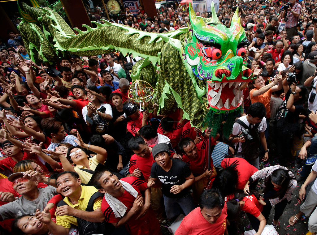 . Revelers try to catch cash envelopes and other items being given away following a dragon and lion performances in front of a grocery store in celebration of Chinese New Year at Manila\'s Chinatown district of Binondo,  Philippines, Friday, Jan. 31, 2014. This year in the Chinese Lunar calendar is the Year of the Horse. (AP Photo/Bullit Marquez)