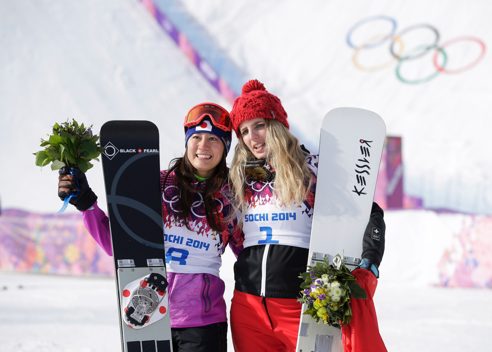 . Women\'s snowboard parallel giant slalom gold medalist Switzerland\'s Patrizia Kummer, right, celebrates with silver medalist Tomoka Takeuchi of Japan after the flower ceremony at the Rosa Khutor Extreme Park, at the 2014 Winter Olympics, Wednesday, Feb. 19, 2014, in Krasnaya Polyana, Russia. (AP Photo/Andy Wong)