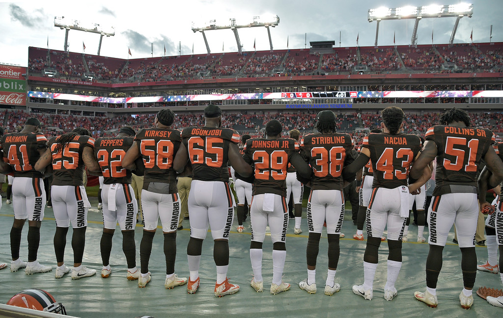 . Cleveland Browns players lock arms during the playing of the national anthem before an NFL preseason football game against the Tampa Bay Buccaneers Saturday, Aug. 26, 2017, in Tampa, Fla. (AP Photo/Phelan M. Ebenhack)