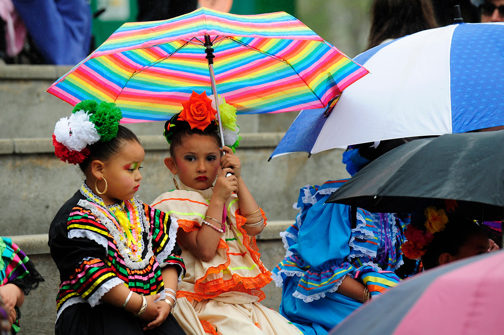 . Dancers Lillyana Ribota (left) and  Adriana Juarez (right) sit under an umbrella before preforming during the 29th Annual Cinco De Mayo Celebration at Civic Center Park in downtown Denver, Colorado, Saturday, May 7, 2016. Festivities were hampered by afternoon showers and some hail on Saturday, however festivities will continue on Sunday. (Brenden Neville/Special to the Denver Post)