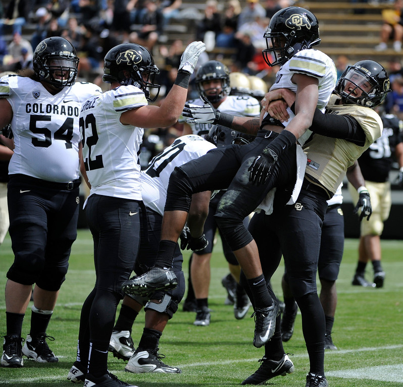 . BOULDER, CO.- APRIL13: White QB Nick Hirschman, right, grabs receiver Jeff Thomas after Thomas scores his TD. The University of Colorado football team hosts its spring football game at Folsom Field under the direction of new head coach Mike MacIntyre. (Photo By Kathryn Scott Osler/The Denver Post)