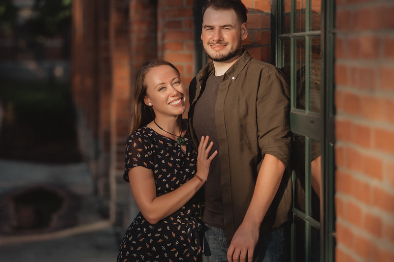 A couple smiling and standing next to a brick wall as a sunbeam illuminates their faces.
