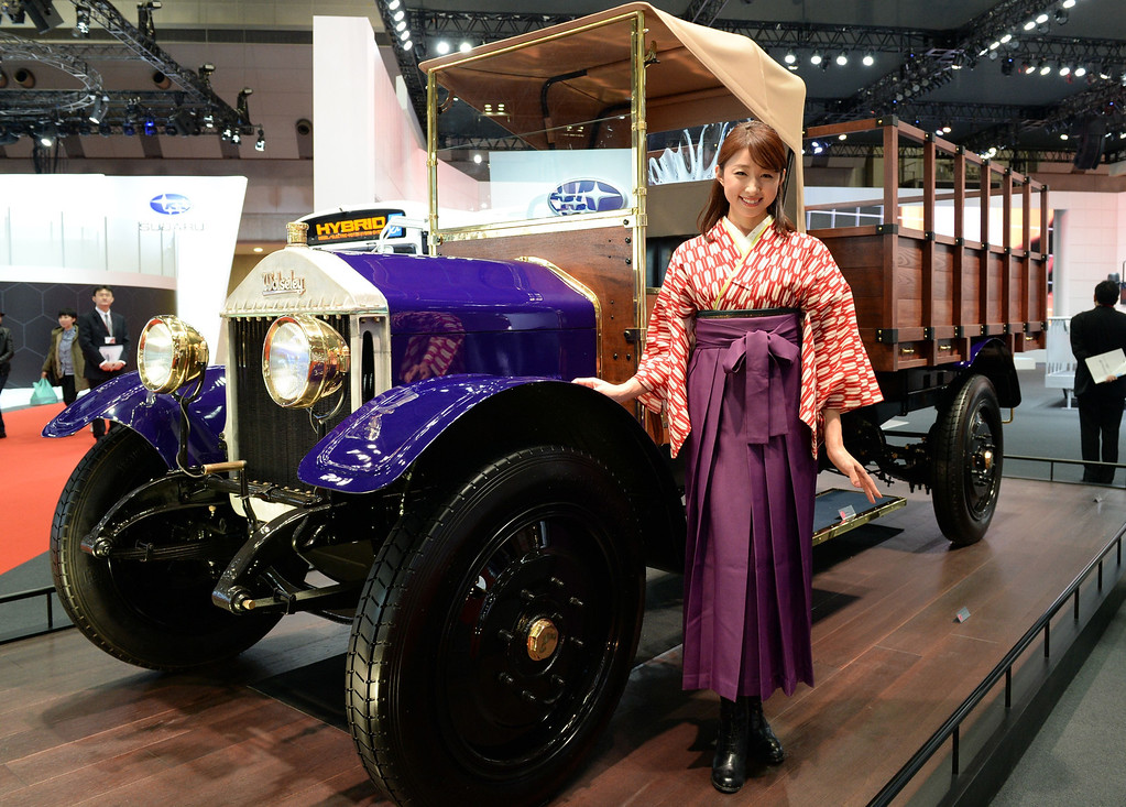 . A model stands beside a 1924 Wolseley CP 1.5-ton truck at the Isuzu booth during the Tokyo Motor Show in Tokyo on November 20, 2013.          AFP PHOTO / TOSHIFUMI KITAMURA/AFP/Getty Images