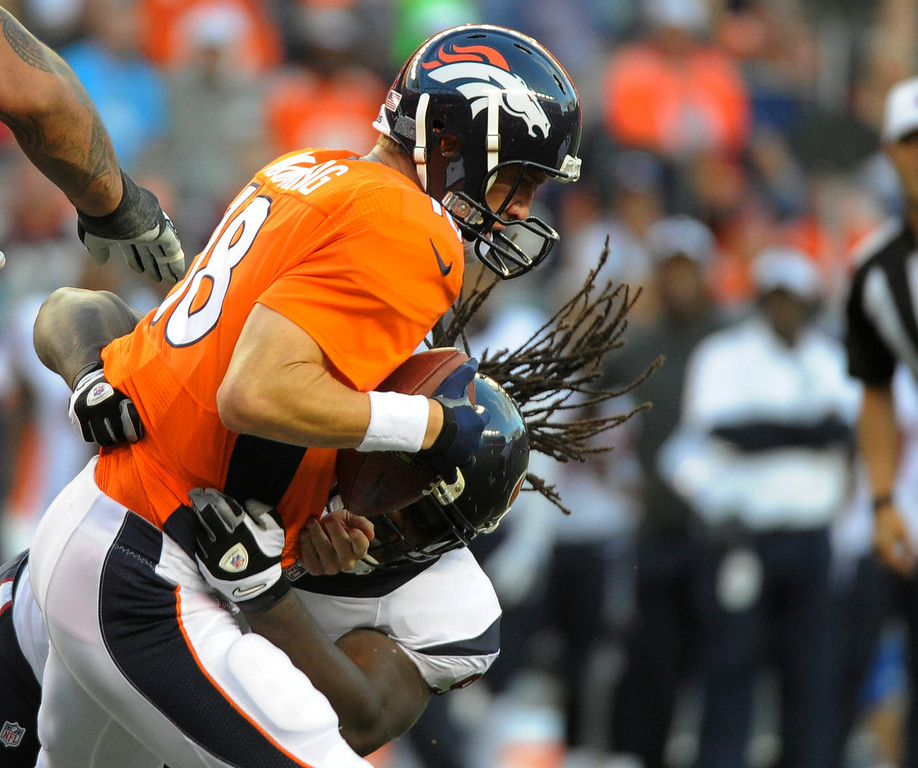 . DENVER, CO - AUGUST 23: Denver Broncos quarterback Peyton Manning (18) gets sacked by Houston Texans defensive tackle Ricardo Mathews (94) during the first quarter August 23, 2014 at Sports Authority Field at Mile High Stadium. (Photo by John Leyba/The Denver Post)
